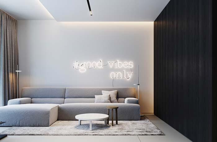 Como decorar uma sala moderna com sofá cinza, parede preta e letreiro neon.