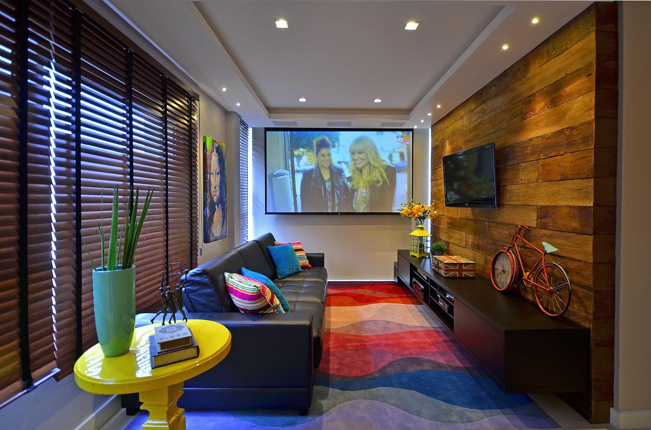 Como decorar uma sala moderna com sofá de couro, tapete colorido e painel de madeira rústica.