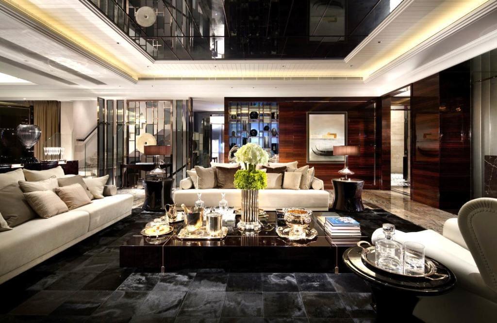 Como decorar uma sala luxuosa com sofá branco, mesa de centro preta e forro decorado.