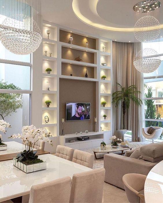Como decorar uma sala luxuosa com pé direito alto, lustres e nichos iluminados.