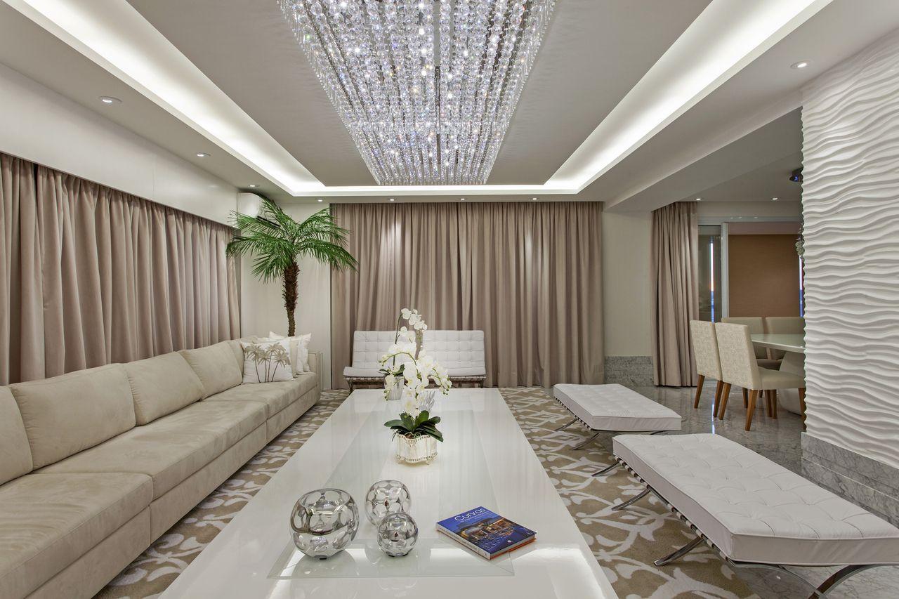 Como decorar uma sala luxuosa com sofá bege, lustre e sanca de gesso.