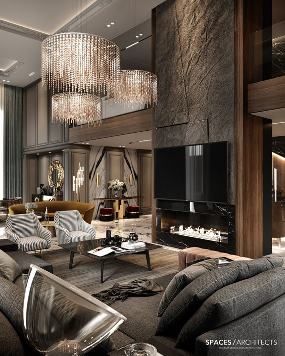 Como decorar uma sala luxuosa escura com lustre moderno, poltronas e lareira com acabamento de porcelanato.