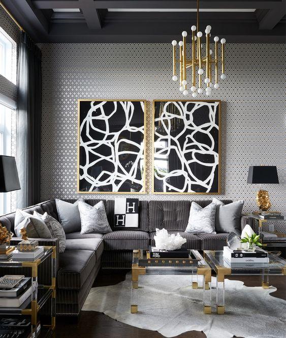 Como decorar uma sala luxuosa com lustre moderna, mesa de centro transparente e sofá cinza.