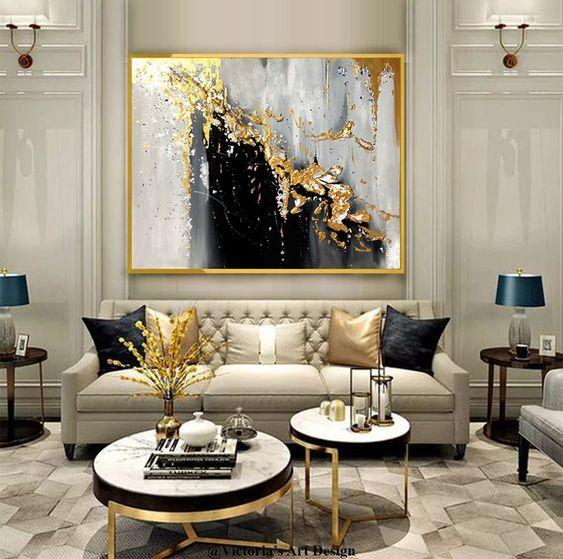 Como decorar uma sala luxuosa com sofá bege e decoração dourada.