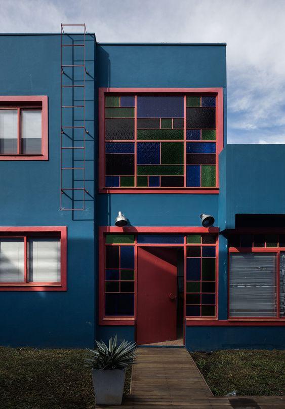 Casa escura azul com detalhes rosa e vidros coloridos.