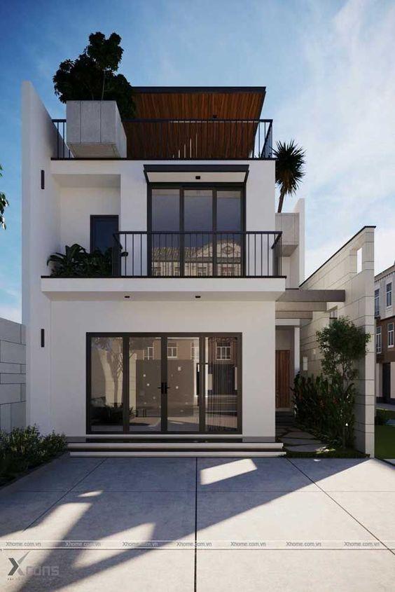 Casa de três andares branca com deatlhes pretos e plantas.
