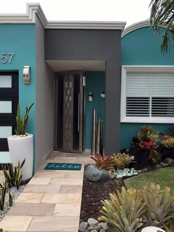 Casa verde com arco da entrada em cinza.