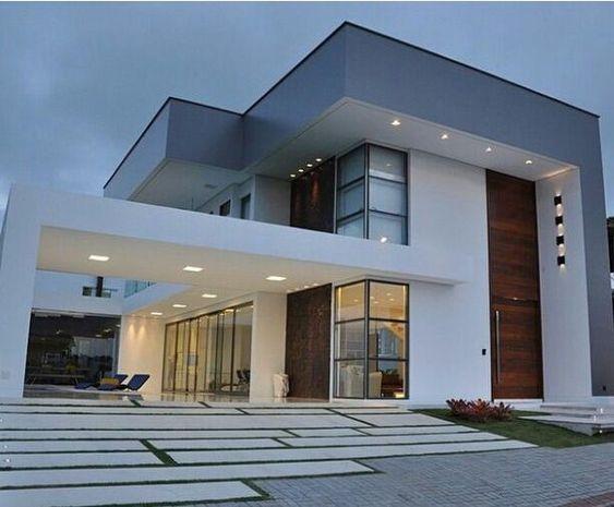 Casa branca e cinza com detalhes de madeira e iluminação embutida.