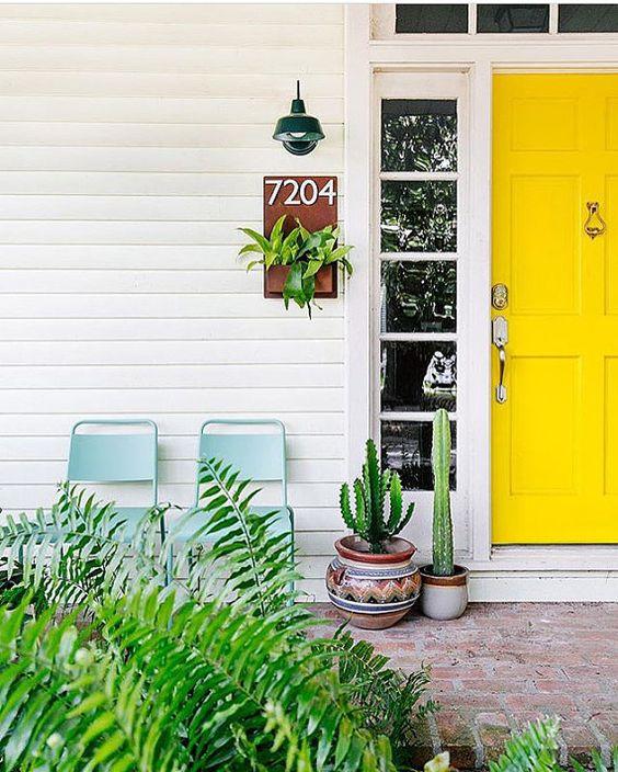Casa branca com plantas e porta amarela.
