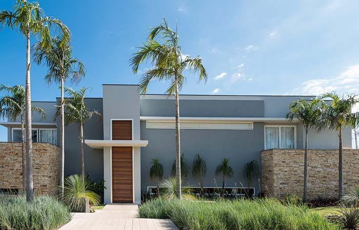 Casa grande com dois tons de cinza e porta grande de madeira.