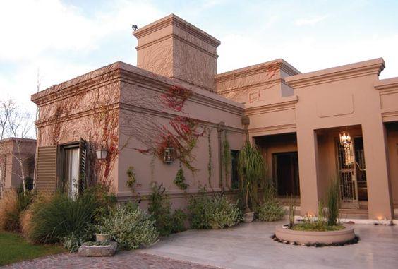 Casa rosê com muitas plantas e trepadeira.