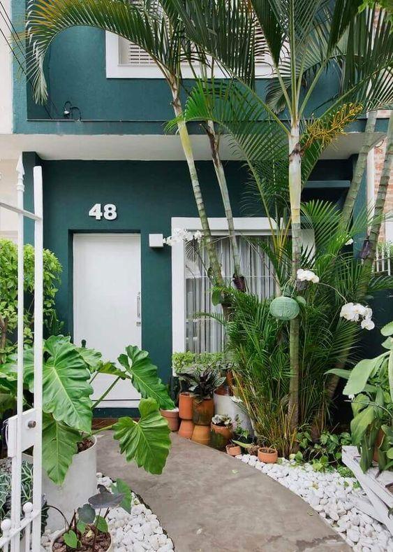 Entrada com jardim dos dois lados e casa verde.
