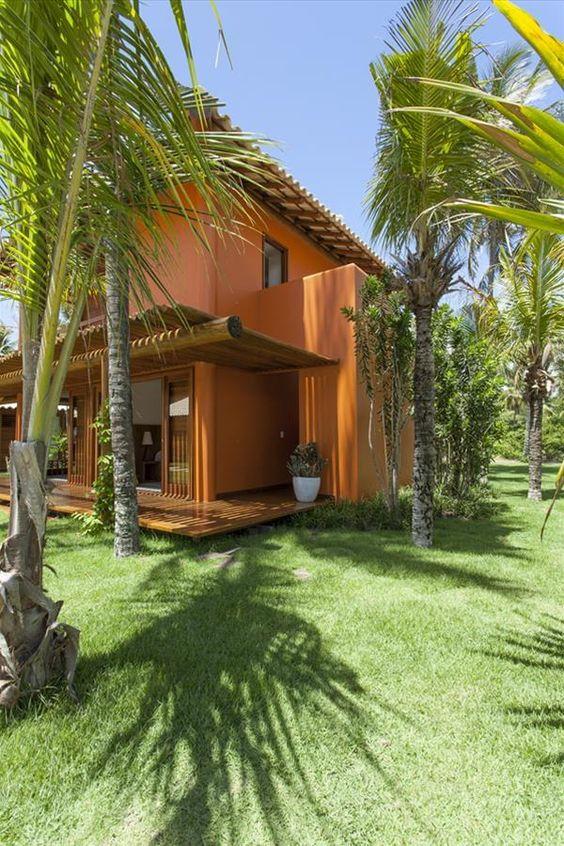 Casa de campo laranja em meio a palmeiras e coqueiros.