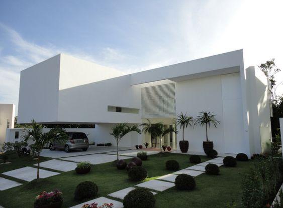 Casa brande e branca com jardim na frente.