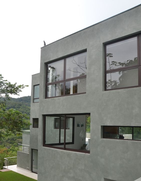 Cores de casas em tons de cinza e cimento queimado dão um toque de seriedade à fachada.