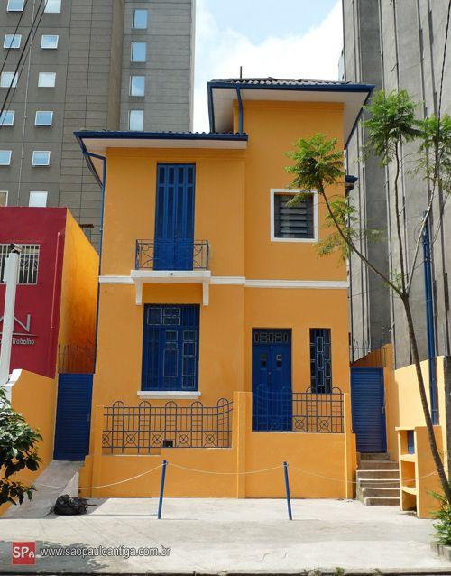Sobrado laranja com janelas e portas azuis.
