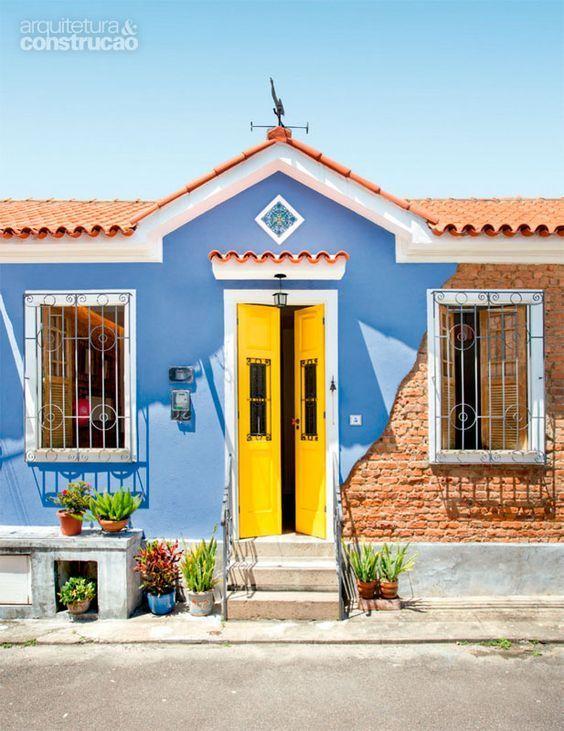 Casa antiga em amarelo, azul e cor de tijolos.