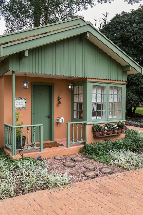 Casa simples de arquitetura clássica em rosa com detalhes verdes.