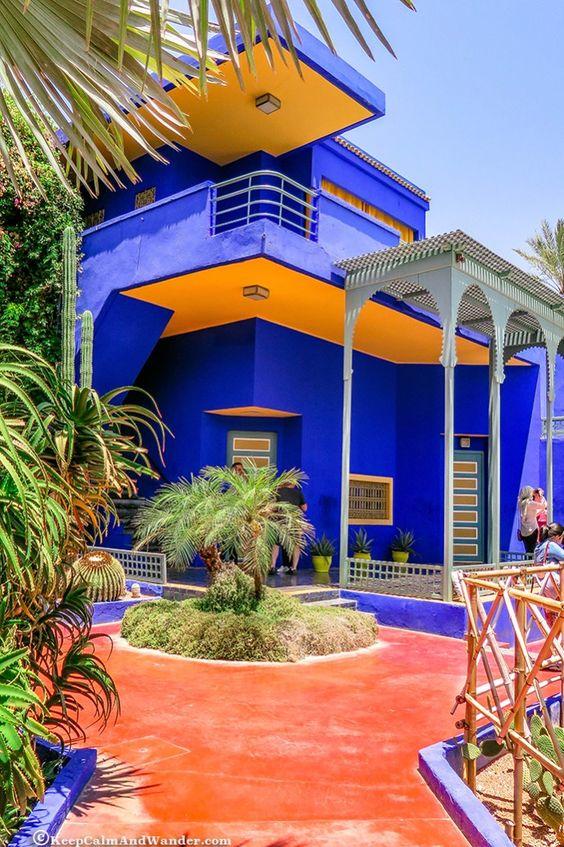 Sobrado azul com teto amarelos e muitas plantas.