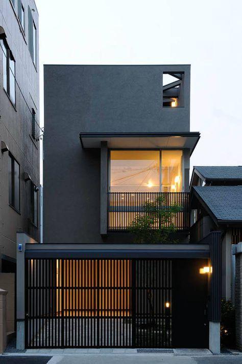 Casa preta com varanda e grades pretas.