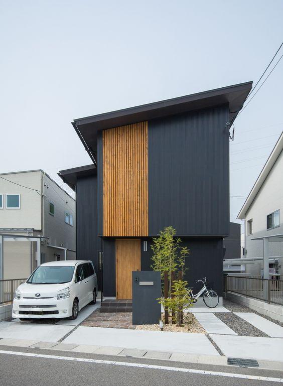 Cores de casas escuras com um pequeno jardim na entrada.