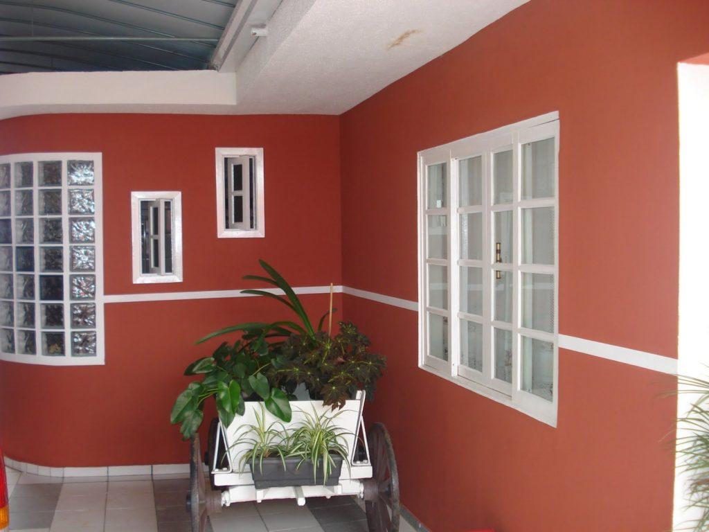 Área externa coberta com paredes vermelhas com detalhes brancos.