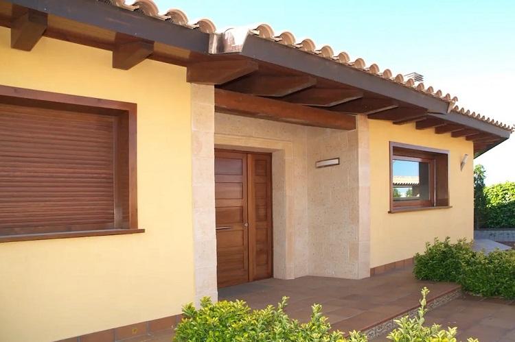 Casa com revestimento na entrada e detalhes marrons.