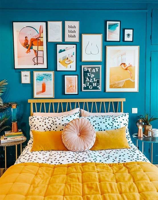 Quarto com parede azul e quadros coloridos.