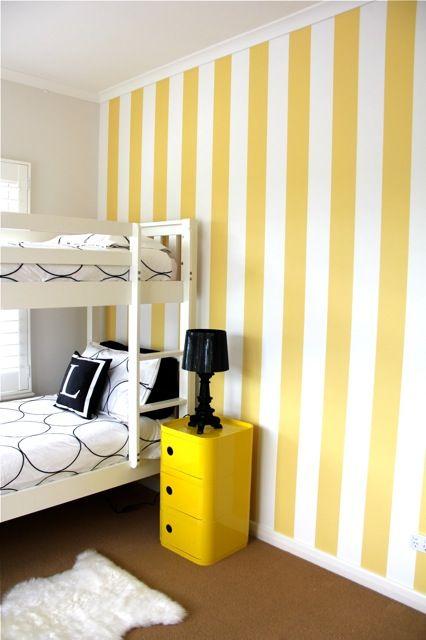 Quarto com papel de parede em amarelo e branco.
