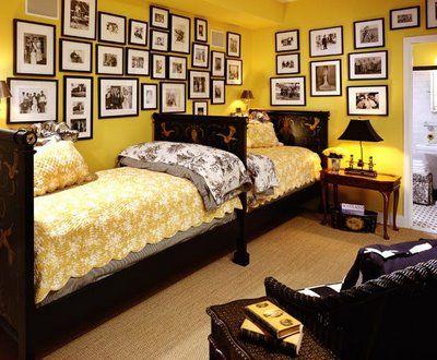 Quarto amarelo com duas camas e muitos quadros com fotos.
