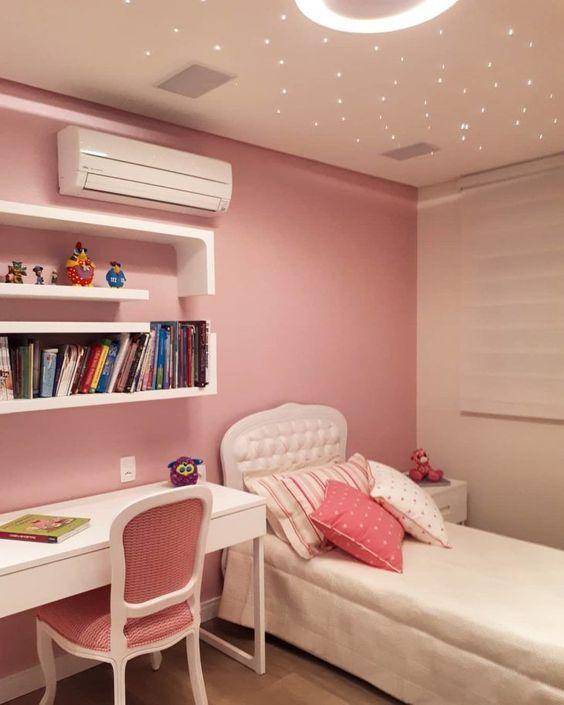 Quarto simples rosa com móveis brancos.