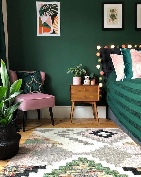 Quarto com parede verde e poltrona rosa.