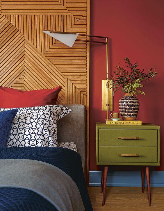 Quarto com parede vermelha e mesa de cabeceira verde.
