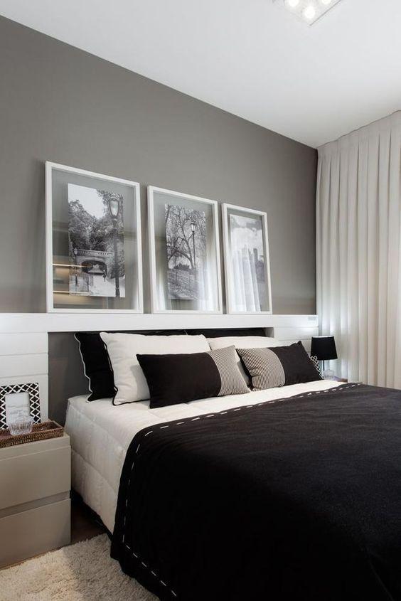 Quarto com parede cinza com roupa de cama em preto e branco.