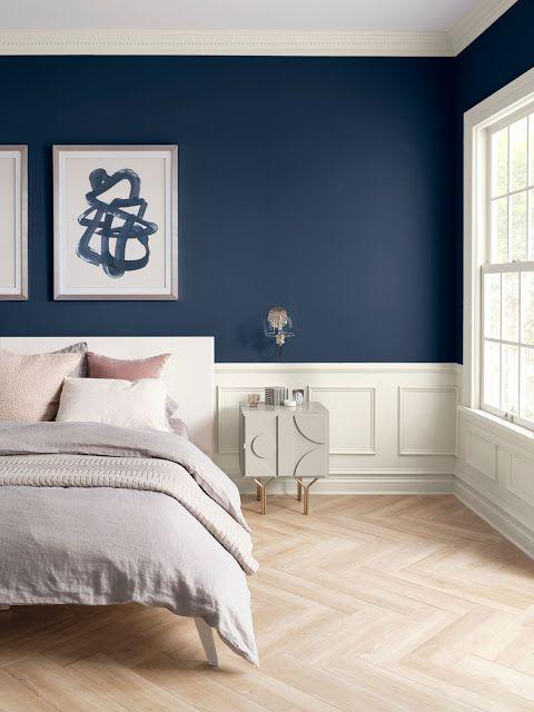 Quarto com paredes em azul marinho e branco.