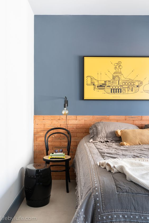 Quarto com parede destacada azul e quadro amarelo.