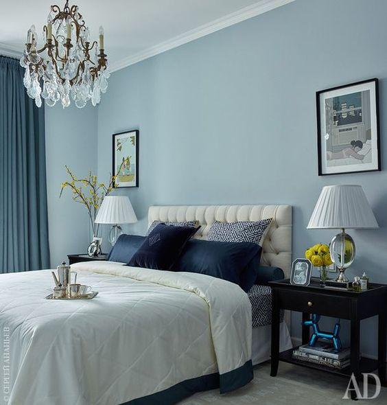 Quarto de casal azul decorado com quadros e abajur.