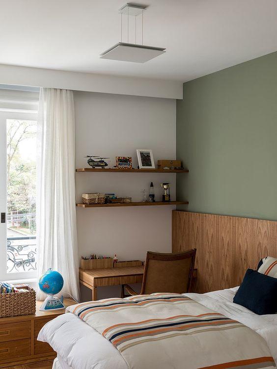 Quarto verde com móveis de madeira.
