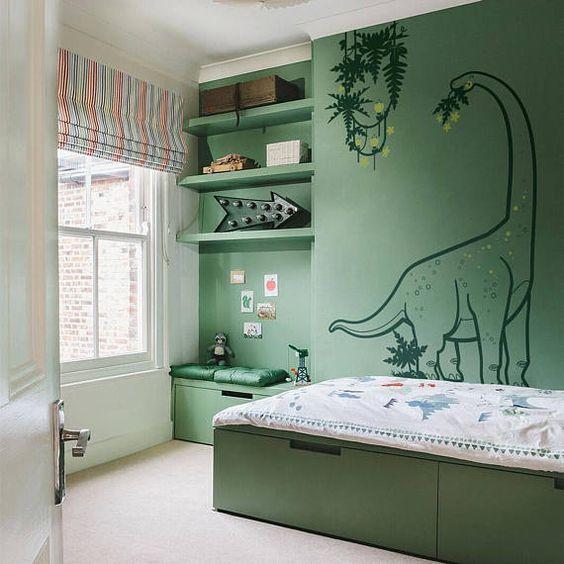 Quarto infantil verde com papel de parede de um dinossauro.