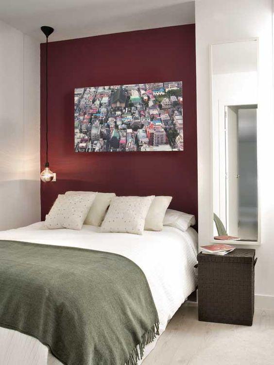 Quarto de casal com uma parede roxa e um quadro de foto de uma cidade.