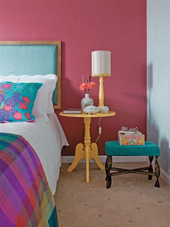 Cores para quarto de casal com paredes rosa e azul e móvel amarelo.