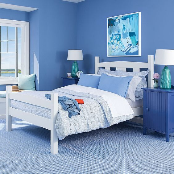 Quarto com paredes e mesas de cabeceira azuis.