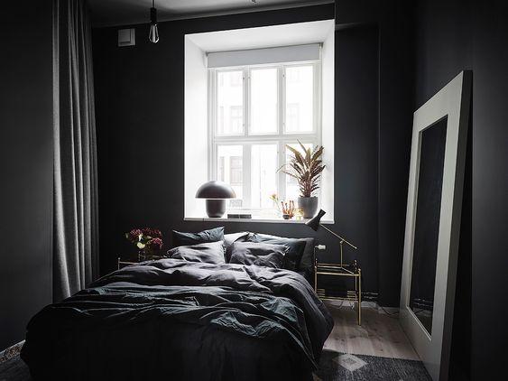 Quarto preto com janela branca.