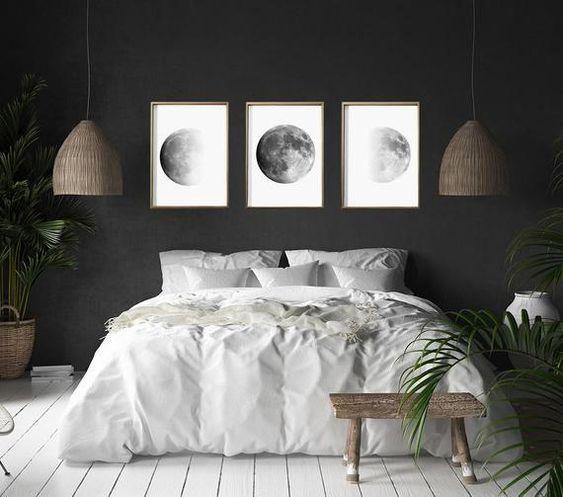 Parede preta com três quadros da lua.