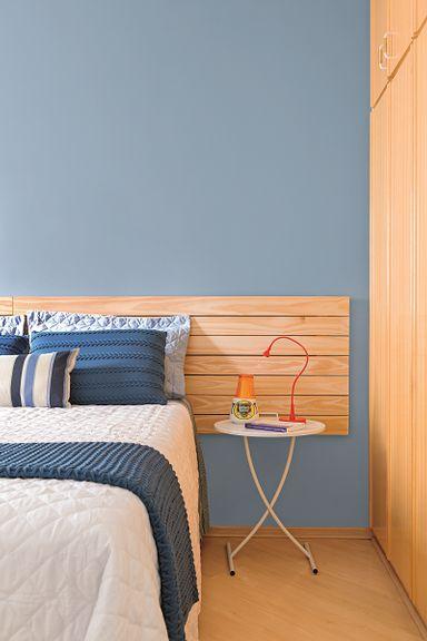 Quarto de casal azul com cabeceira da cama de madeira.