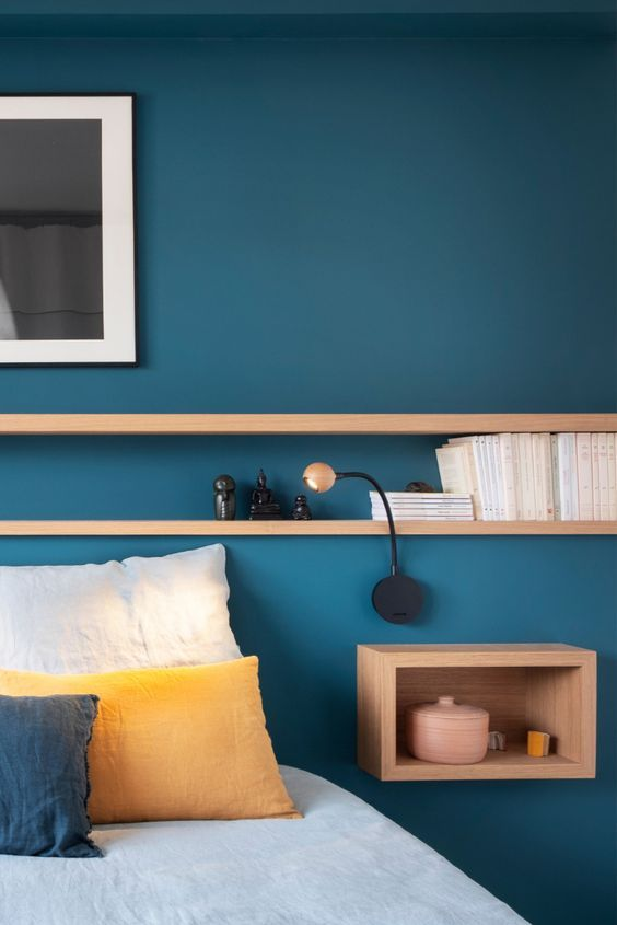 Quarto azul com nichos de madeira.