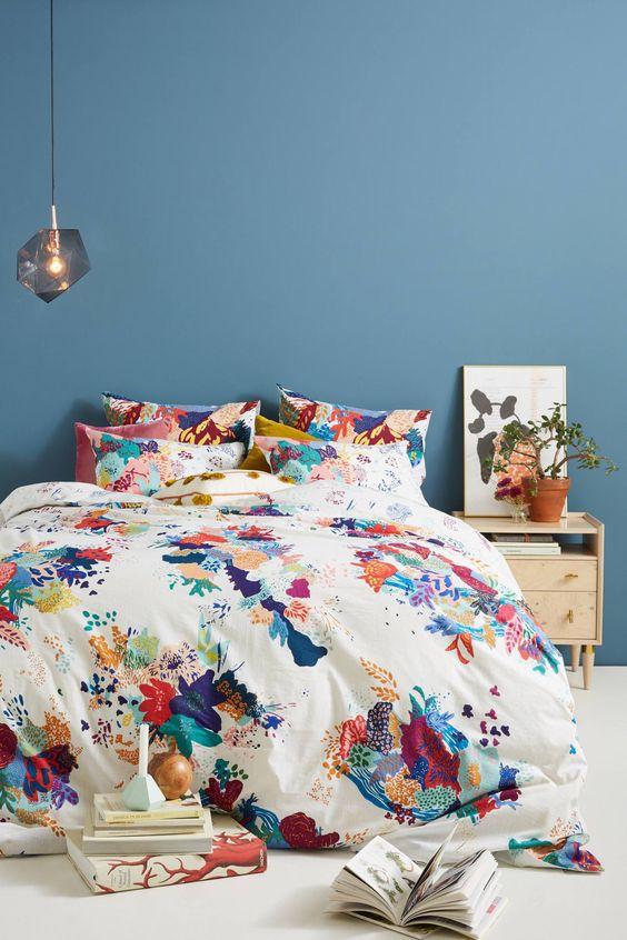 Cores para quarto de casal: parede azul com roupa de cama colorida.