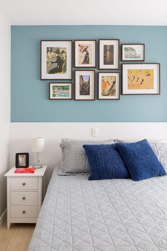 Parede azul e branca com quadros coloridos.