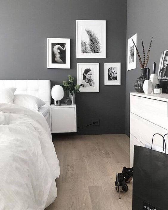 Paredes cinzas com quadros em preto e branco.