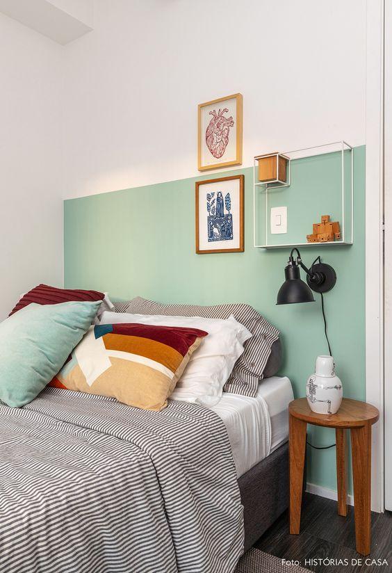 Parede verde e branca com artigos decorativos.